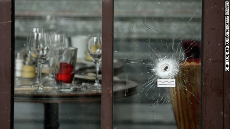 Bullets holes are seen through the glass door of a cafe near Casa Nostra on November 14.