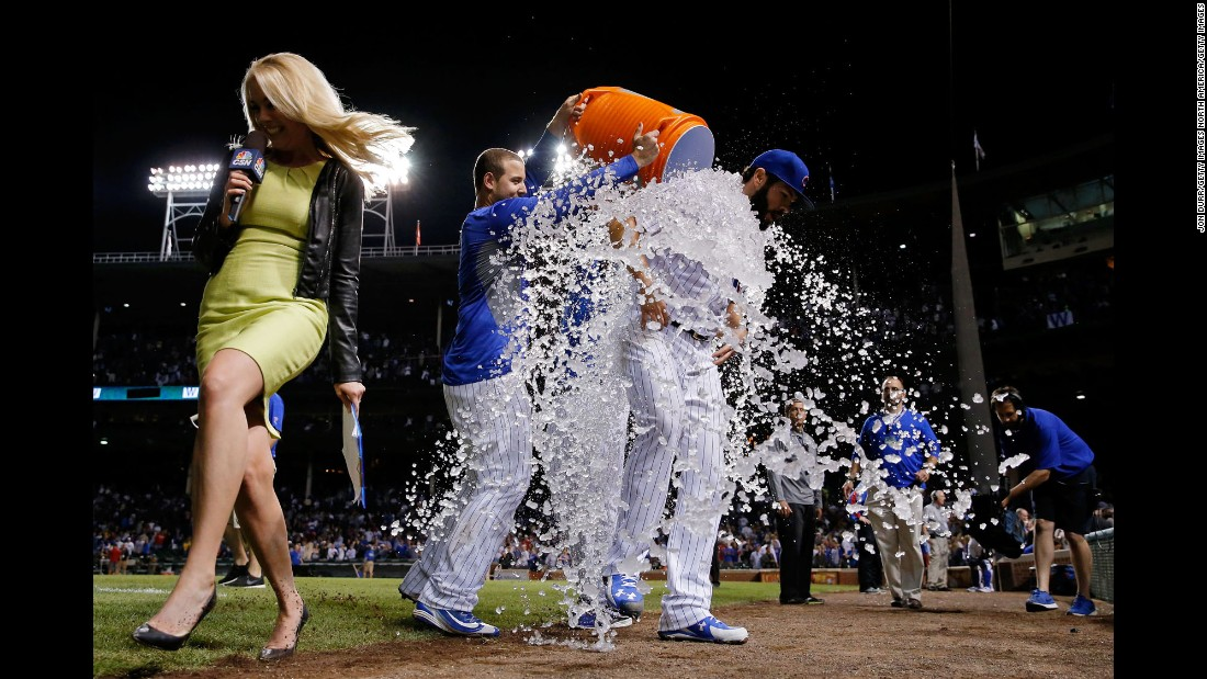 Television reporter Kelly Crull runs away from the scene as Chicago Cubs pitcher Jake Arrieta is doused by his teammates after his 20th win of the season on Tuesday, September 22. Arrieta finished with 22 wins in the regular season and won the National League's Cy Young Award.