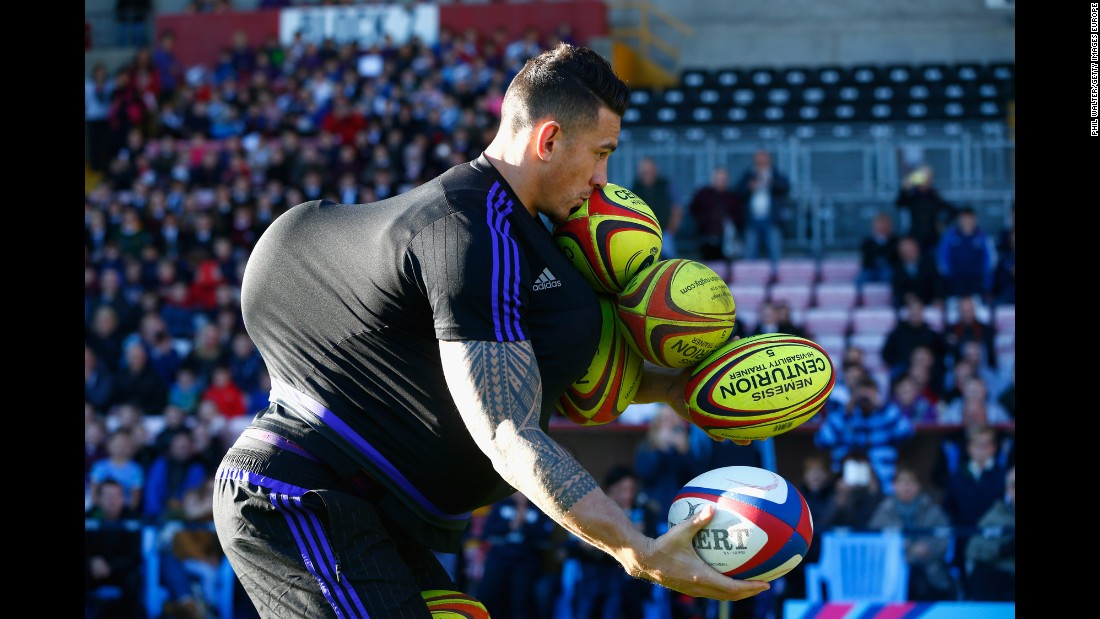 New Zealand rugby player Sonny Bill Williams tries to carry as many balls as he can during a community event in Darlington, England, on Thursday, October 8.