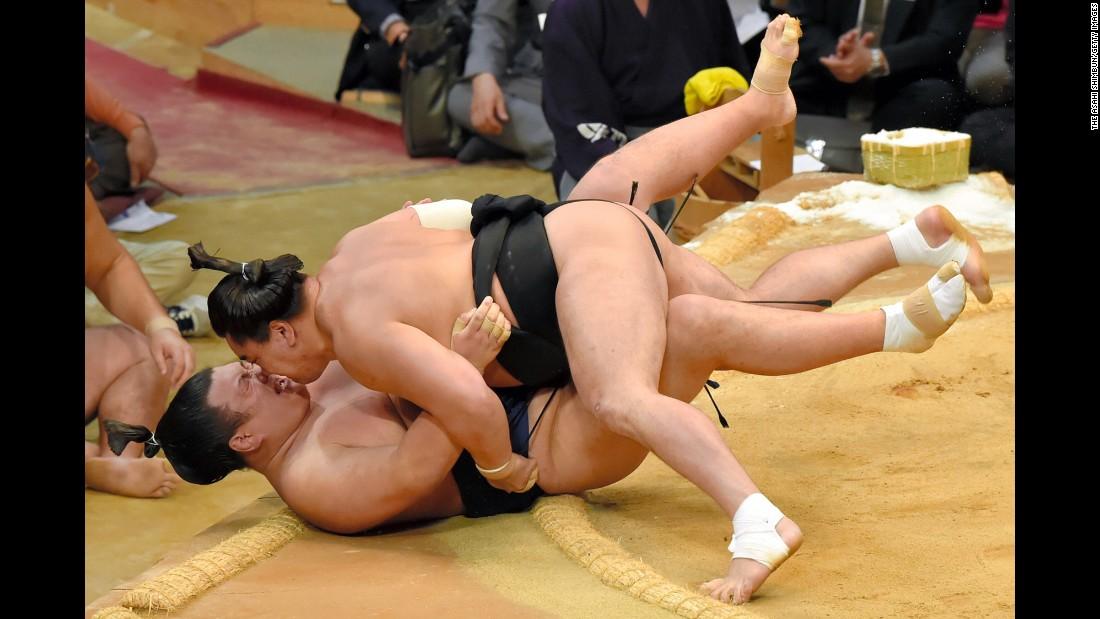 Mongolian sumo wrestler Harumafuji lands on Ikioi during a tournament in Fukuoka, Japan, on Monday, November 16.