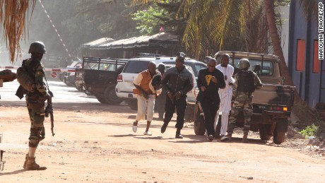 People flee from the Radisson Blu Hotel in Bamako, Mali on Friday, November 20, amid reports of a hostage situation.