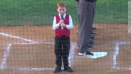 A young boy receives congratulations from all after he delivers a stunning rendition of Australia's national anthem while battling an onset of hiccups.