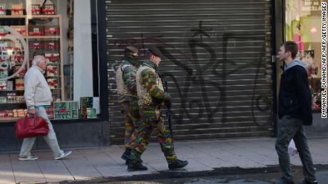 Soldiers patrol past closed shops as the Belgian capital remains on the highest possible alert level on November 23, 2015 in Brussels. Brussels began a third consecutive day in lockdown under a maximum terror alert after Belgian police staged a series of raids but failed to find a key Paris attacks suspect. AFP PHOTO/Emmanuel DunandEMMANUEL DUNAND/AFP/Getty Images