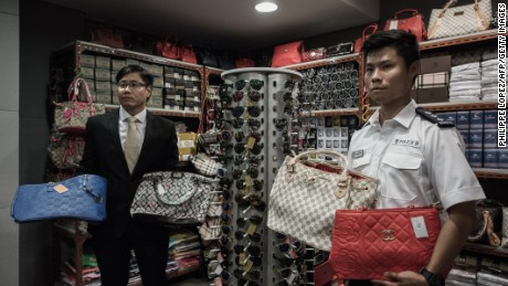 Counterfeit luxury goods are displayed by customs (L) and police (R) officials following a record seizure at the customs headquarters in Hong Kong on August 6, 2015. Hong Kong authorities said they smashed a syndicate suspected of selling counterfeit goods, in an operation that made a record seizure in terms of quantity among similar cases in a decade.  AFP PHOTO / Philippe Lopez        (Photo credit should read PHILIPPE LOPEZ/AFP/Getty Images)