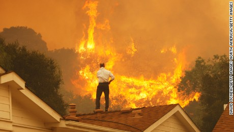 CAMARILLO, CA - MAY 3:  A man on a rooftop looks at approaching flames as the Springs fire continues to grow on May 3, 2013 near Camarillo, California. The wildfire has spread to more than 18,000 acres on day two and is 20 percent contained.  (Photo by David McNew/Getty Images)