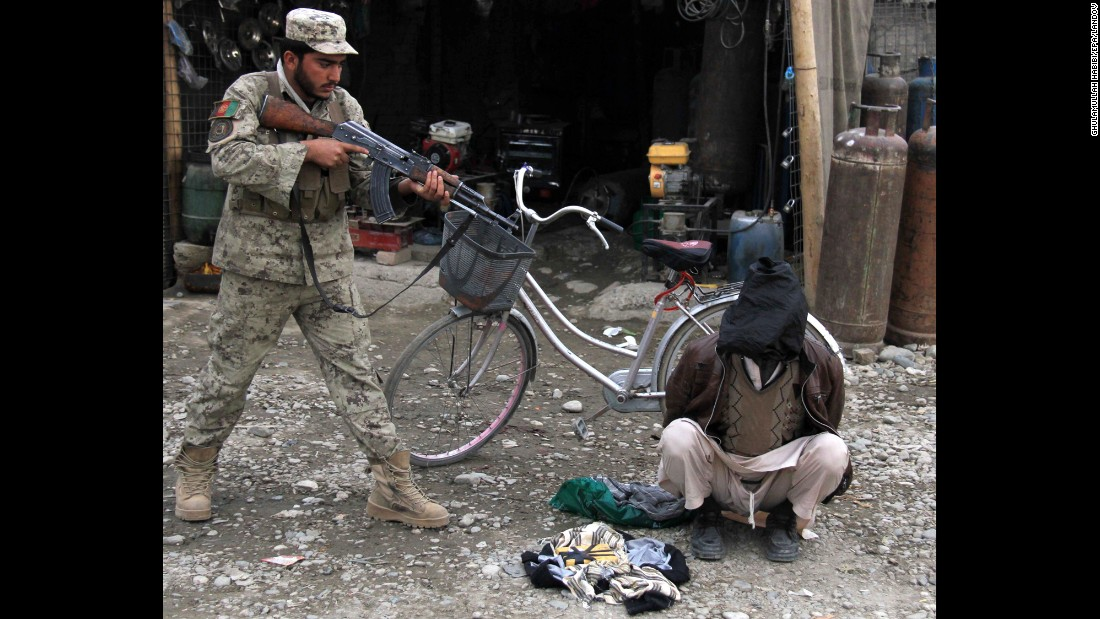 <strong>January 20:</strong> An Afghan security officer aims his weapon at a man who was allegedly planning a suicide bomb attack in Jalalabad, Afghanistan.