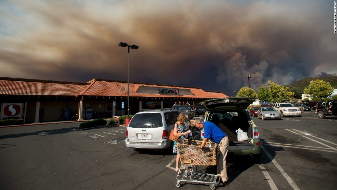 "<strong>August 2:</strong> Shoppers load groceries as smoke from the Rocky Fire billows over Clearlake, California. California <a href=""http://www.cnn.com/2015/07/18/us/gallery/ca-wildfire-2015/index.html"" target=""_blank"">has been battling numerous wildfires</a> as its historic drought reaches a fourth year."