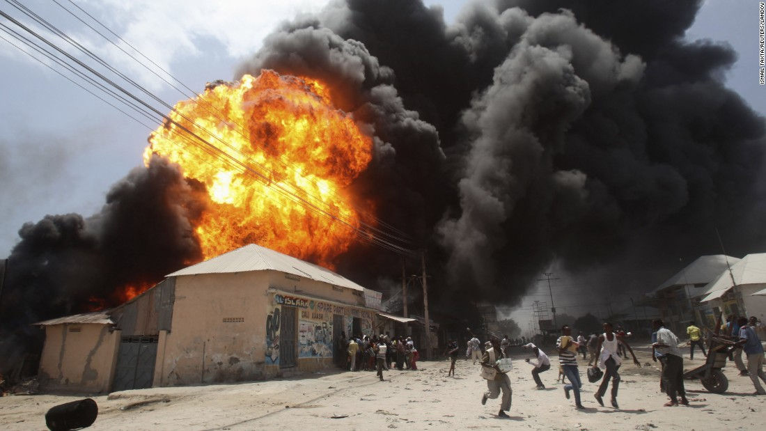 <strong>February 23:</strong> People run from an explosion at a gas station and storage facility near the Bakara market in Mogadishu, Somalia.