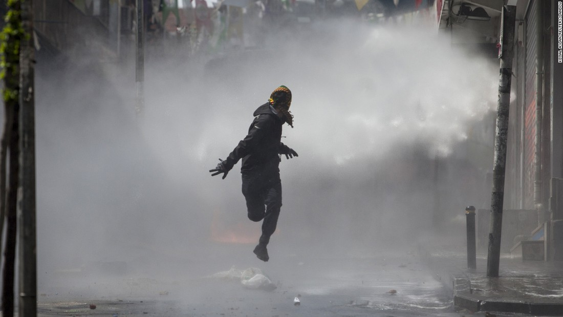 "<strong>May 1:</strong> A masked protester runs away as police use water cannons on May Day demonstrators in Istanbul. Clashes erupted between police and protesters who defied a government ban on marching to Taksim Square. <a href=""http://www.cnn.com/2015/05/01/world/gallery/may-day-pictures-2015/index.html"" target=""_blank"">May Day</a> is referred to as International Workers' Day in many countries."