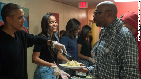 Malia Obama (2nd L), daughter of US President Barack Obama (L), smiles as they serve Thanksgiving dinner to homeless military veterans with First Lady Michelle Obama (3rd L) and daughter Sasha at Friendship Place in Washington, DC, on November 25, 2015.