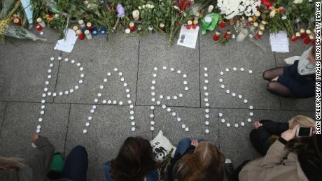 """BERLIN, GERMANY - NOVEMBER 14:  People finish arranging candles into the word """"Paris"""" next to flowers and messages left at the gate of the French Embassy following the recent terror attacks in Paris on November 14, 2015 in Berlin, Germany. Hundreds of people came throughout the day to lay flowers, candles and messages of condolence to mourn the victims of attacks last night in Paris that left at least 120 people dead across the French capital. The Islamic State (IS) has claimed responsibility for the attacks that were carried out by at least eight terrorists..  (Photo by Sean Gallup/Getty Images)"""