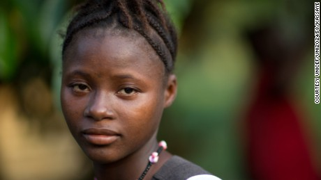 [NAME CHANGED] On 14 November 2015, Amina Kamara, 15, stands in the yard of her home,  behind her is her husband Lamine, in Motonko Village, Ribbi Chiefdom, Moyamba District.