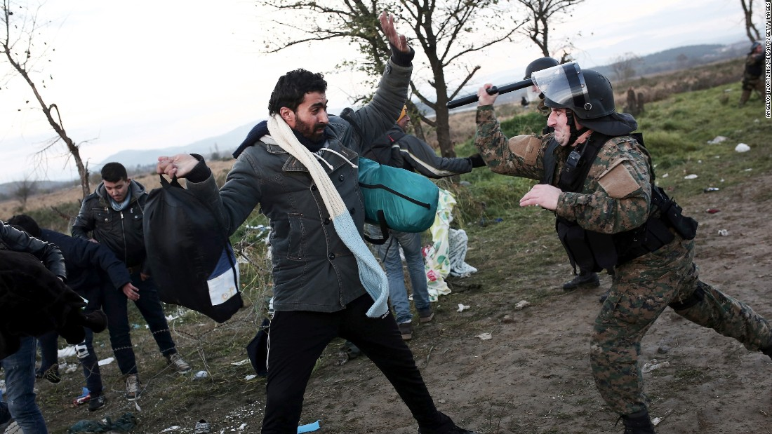 A Macedonian police officer hits a man with his baton near Idomeni at the Greek-Macedonian border -- this is part of the so-called Balkans Route to northern Europe.