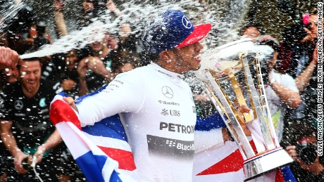 AUSTIN, TX - OCTOBER 25:  Lewis Hamilton of Great Britain and Mercedes GP celebrates with the team in the pit lane after winning the United States Formula One Grand Prix and the championship at Circuit of The Americas on October 25, 2015 in Austin, United States.  (Photo by Clive Mason/Getty Images)