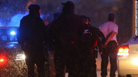 COLORADO SPRINGS, CO - NOVEMBER 27:  A suspect is led away in handcuffs by police during an active shooter situation outside a Planned Parenthood facility where an active shooter reportedly injured up to eleven people, including at least five police officers, on November 27, 2015 in Colorado Springs, Colorado.  Police continue to investigate the scene and are searching the buiding for possible explosive devices. (Photo by Justin Edmonds/Getty Images)