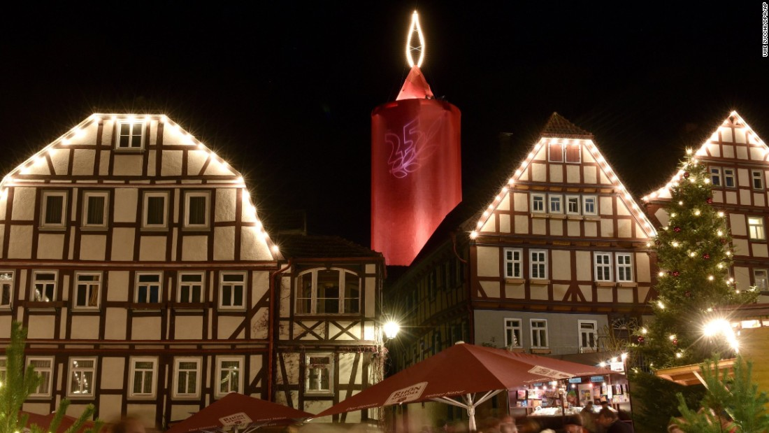 Timber-framed buildings are illuminated in front of a giant candle tower in Schlitz, Germany. The 36-meter (118-foot) tower dominates the Christmas market.