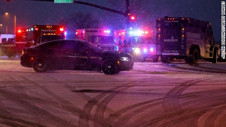 A police vehicle carrying a suspect  drives away from the scene during an active shooter situation outside a Planned Parenthood facility where an active shooter reportedly injured up to eleven people, including at least five police officers, on November 27, 2015 in Colorado Springs, Colorado.