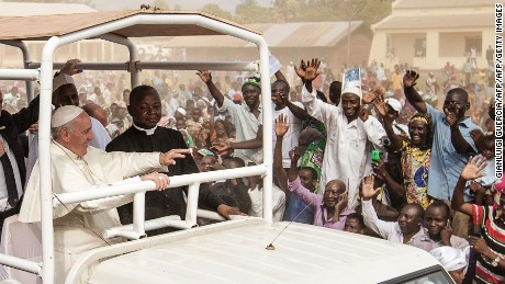 "Pope Francis (C) waves as he visits the Koudoukou school, to meet people from the muslim community, after leaving the Central Mosque in the PK5 neighborhood on November 30, 2015 in Bangui. Pope Francis on November 30 said Christians and Muslims were ""brothers"", urging them to reject hatred and violence on a visit to a mosque in a flashpoint Muslim neighbourhood of the Central African Republic's capital Bangui. AFP PHOTO / GIANLUIGI GUERCIA / AFP / GIANLUIGI GUERCIA        (Photo credit should read GIANLUIGI GUERCIA/AFP/Getty Images)"
