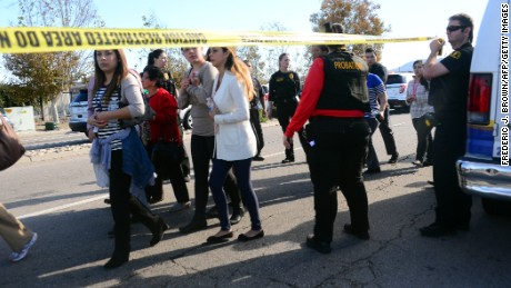 Survivors are evacuated from the scene of a shooting under police and sheriff's escort on December 2, 2015 in San Bernadino, California.  One or more gunman opened fire inside a building in San Bernardino in California, with reports of 20 victims at a center that provides services for the disabled. Police were still hunting for the shooter, saying one to three possible suspects were involved. Heavily armed SWAT teams, firefighters and ambulances swarmed the scene, located about an hour east of Los Angeles, as police warned residents away.  AFP PHOTO / FREDERIC J. BROWN / AFP / FREDERIC J. BROWN        (Photo credit should read FREDERIC J. BROWN/AFP/Getty Images)
