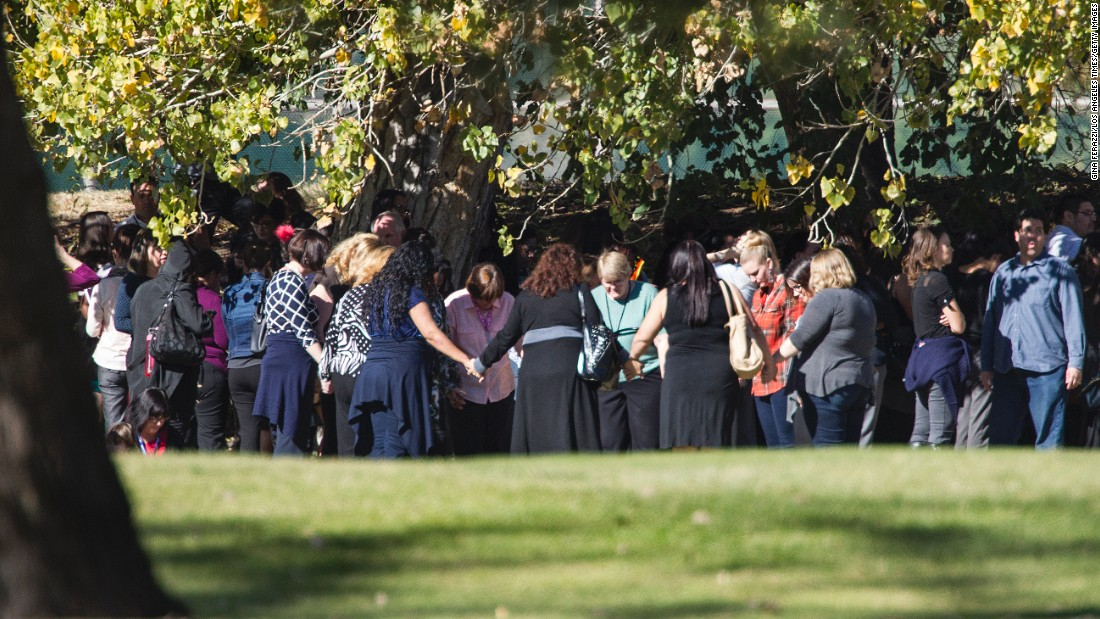People pray on the San Bernardino Golf Course, across the street from where the shooting took place.