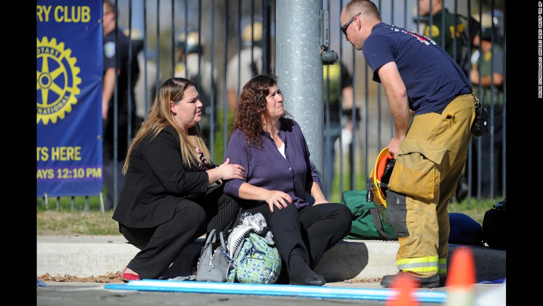 Two women speak with a firefighter at a triage area near the scene.