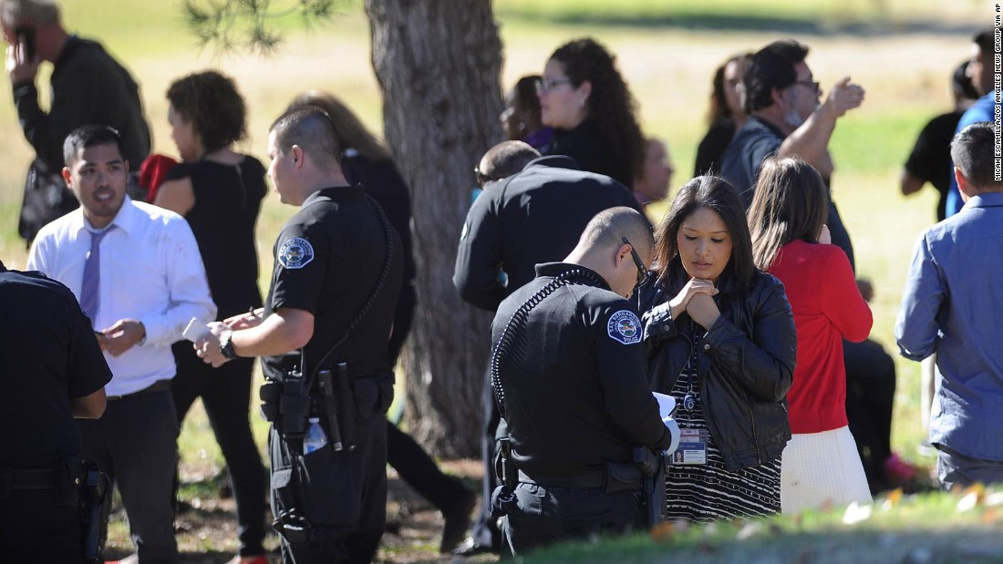 People talk to police at the golf course.