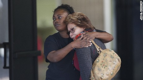 Two women embrace with a neighborhood middle where loved ones had been gathering to pick up survivors.
