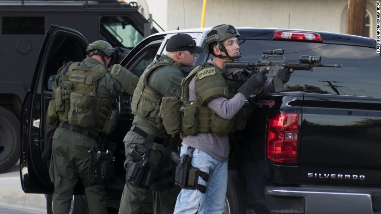 Law enforcement officers search a neighborhood in San Bernardino.