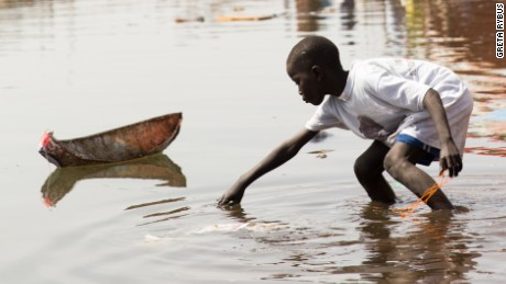 A small boy plays using a homemade toy boat. Next the end of the period the sea withdraws back and individuals contact that point Ndey.