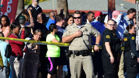 A crowd gathers behind police line near the scene of a shooting on December 2, 2015 in San Bernardino, California. One or more gunman opened fire inside a building in San Bernardino in California, with reports of 20 victims at a center that provides services for the disabled. Police were still hunting for the shooter, saying one to three possible suspects were involved. Heavily armed SWAT teams, firefighters and ambulances swarmed the scene, located about an hour east of Los Angeles, as police warned residents away.  AFP PHOTO / FREDERIC J. BROWN / AFP / FREDERIC J. BROWN        (Photo credit should read FREDERIC J. BROWN/AFP/Getty Images)
