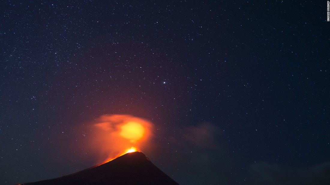 The Momotombo volcano erupts just before daybreak, as seen from the community of El Papalonal, in Leon, Nicaragua, on Friday, December 4. Quiet for many years, the volcano emitted some glowing rock two days before after gas and ash emissions began.