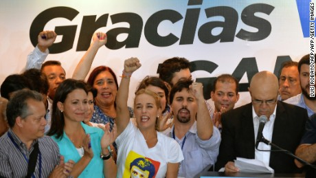 The wife of jailed Venezuelan opposition leader Leopoldo Lopez, Lilian Tintori (C) next to Freddy Guevara (2nd R) of the Voluntad Popular party, smiles after knowing the first results of the legislative election, at the Democratic Unity Movement (MUD) party headquarters in Caracas, on the early morning December 7, 2015. Venezuelan electoral authorities announced that the opposition had won majority in Venezuela legislature.  AFP PHOTO/LUIS ROBAYO / AFP / LUIS ROBAYO        (Photo credit should read LUIS ROBAYO/AFP/Getty Images)