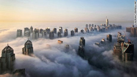 A thick blanket of early morning fog partially shrouds the skyscrapers of the Marina and Jumeirah Lake Towers districts of Dubai. The city's rapid transformation from a desert outpost into one of the world's most architecturally stunning cities is mapped out in the Marina. Where just 15 years ago there was empty, flat land, today a bustling neighborhood thrives centered around a canal and an impressive skyline that pierces through the clouds.