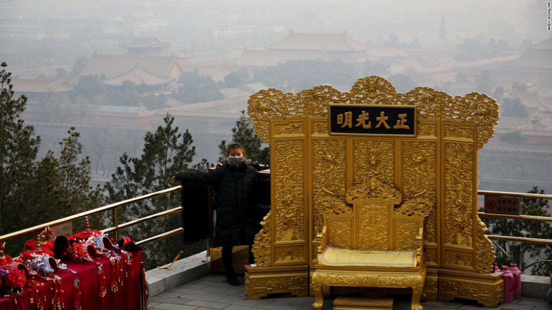 A mask-wearing vendor awaits customers at the Jingshan Park on a polluted day in Beijing on December 7.