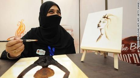 A Saudi woman paints using Arabic coffee during the International Coffee and Chocolate Exhibition in the desert kingdom's capital Riyadh on December 15, 2014. AFP PHOTO / FAYEZ NURELDINE        (Photo credit should read FAYEZ NURELDINE/AFP/Getty Images)