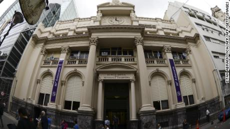 People walk past the facade of the Central Bank of Argentina in downtown Buenos Aires, on November 17, 2015. Metropolitan Police officers and judiciary officials conducted a raid at the Central Bank headquarters as part of an investigation into the alleged sale of future dollars at a lower price than the marked by its president, Alejandro Vanoli. AFP PHOTO/Eitan Abramovich        (Photo credit should read EITAN ABRAMOVICH/AFP/Getty Images)