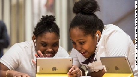 """NEW YORK, NY - DECEMBER 09:  Jiavaennye Green (L) and Taylor Phillips, third grade children from PS 57 James Weldon Johnson Leadership Academy, learn how to code at an Apple Store through Apple's """"Hour of Code"""" workshop program on December 9, 2015 in New York City. Tim Cook, CEO of Apple, visited the students and said he hoped that teaching coding to children would become standard in education throughout the United States.  (Photo by Andrew Burton/Getty Images)"""