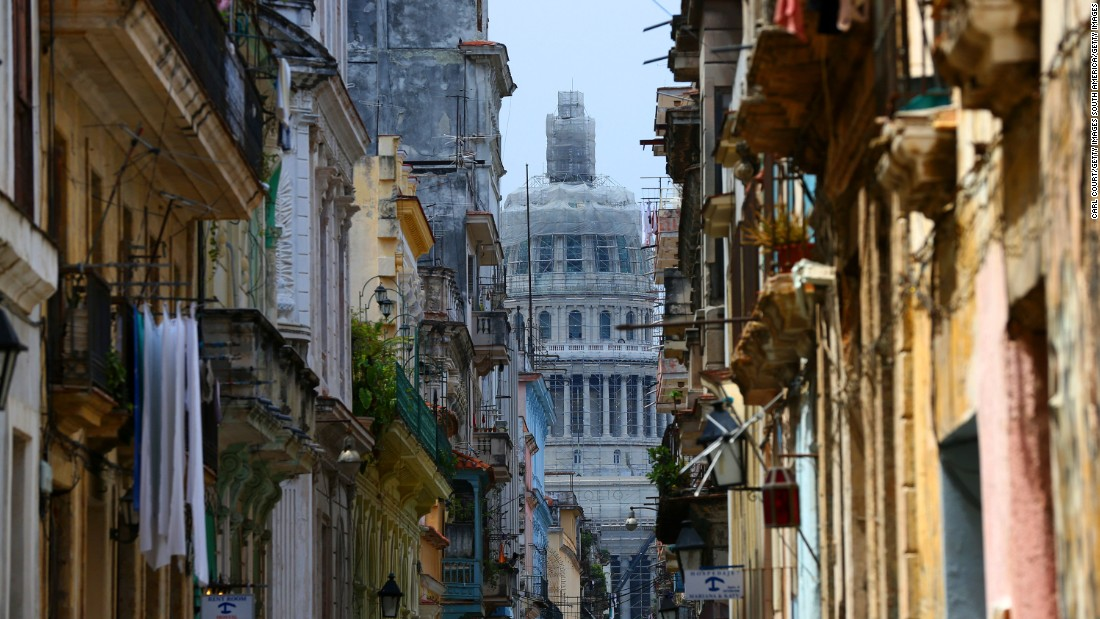 U.S. travelers are eager to visit Cuba to see what they've been missing. Here, a street in Havana provides a peek at the National Capitol Building.