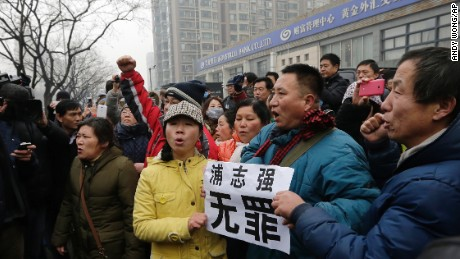 "Supporters of prominent rights lawyer Pu Zhiqiang chant slogans as they gather near the Beijing Second Intermediate People's Court in Beijing, Monday, Dec. 14, 2015. Pu went on trial Monday on charges of provoking trouble with commentaries on social media that were critical of the ruling Communist Party. The placard reads: ""Pu Zhiqiang, innocence."" (AP Photo/Andy Wong)"