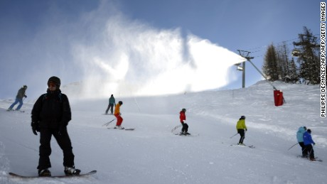 Skiers descend a slope in front of a snow cannon, on December 12, 2012, in Val d'Isere, French Alps. Recent snowfalls have encouraged skiers to hit the slopes and the Val d'Isere authorities have opened certain slopes early.  AFP PHOTO/PHILIPPE DESMAZES        (Photo credit should read PHILIPPE DESMAZES/AFP/Getty Images)