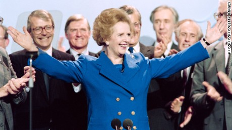 British Prime Minister Margaret Thatcher acknowledges applause on Ocotber 13, 1989, at the end of the Conservative Party conference in Blackpool. At left Foreign Secretary John Major and at right Home Secretary John Hurt. (Photo credit: JOHNNY EGGITT/AFP/Getty Images)