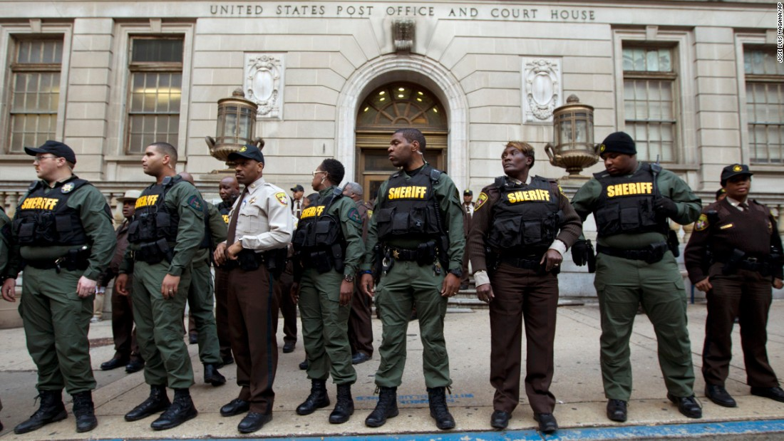 Officers stand guard in front of the courthouse's main entrance as people protest on December 16.