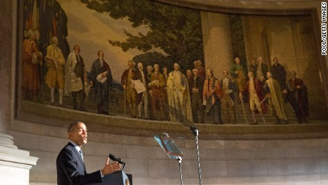 President Barack Obama speaks during a naturalization ceremony for new U.S. citizens beneath a painting of America's founding fathers at the National Archives  December 15, 2015 in Washington, DC.