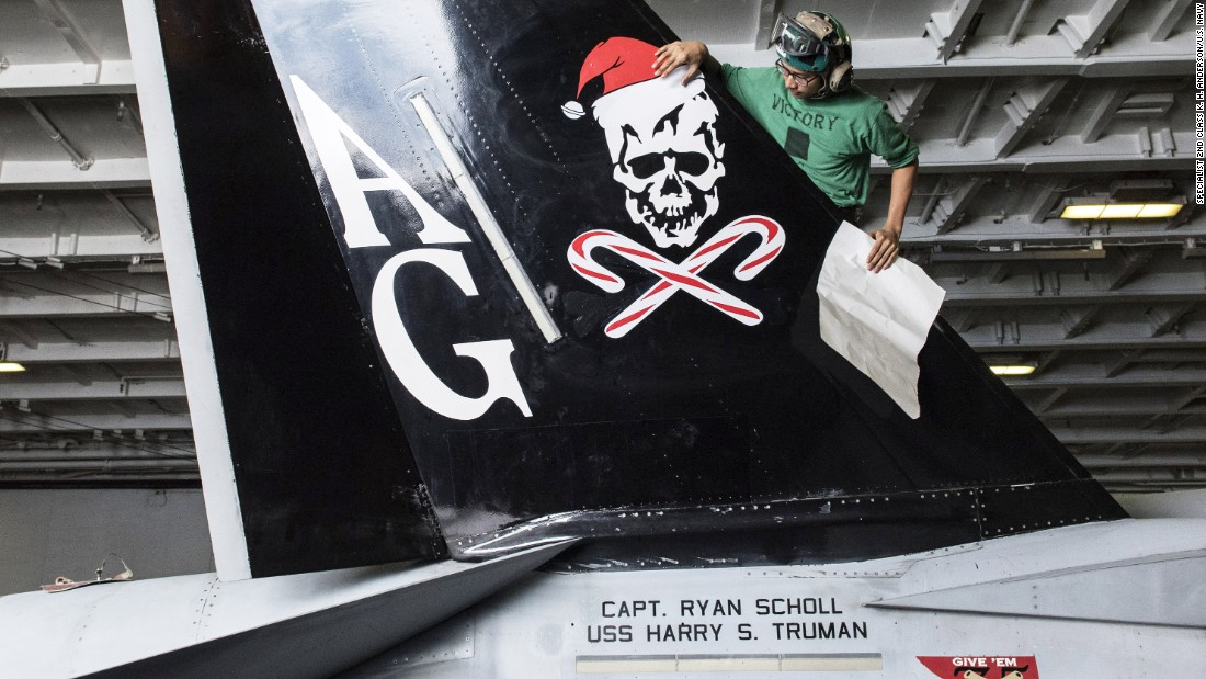 "Aviation Structural Mechanic Airman V. Sek, assigned to the ""Jolly Rogers"" of Strike Fighter Squadron (VFA) 103, applies a Christmas decal to an F/A-18F Super Hornet in the hangar bay of the Nimitz-class aircraft carrier USS Harry S. Truman in December 2015."