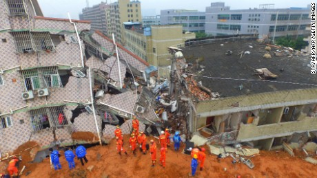 In this aerial photograph, Chinese rescuers work at the site of a landslide that hit an industrial park in Shenzhen in south China's Guangdong province on December 21, 2015. Some 85 people were missing on December 21 after a huge landslide caused by illegal soil dumping buried more than 30 factory and residential buildings in a sea of mud, China's second industrial disaster in four months. CHINA OUT   AFP PHOTO / STR / AFP / STR        (Photo credit should read STR/AFP/Getty Images)