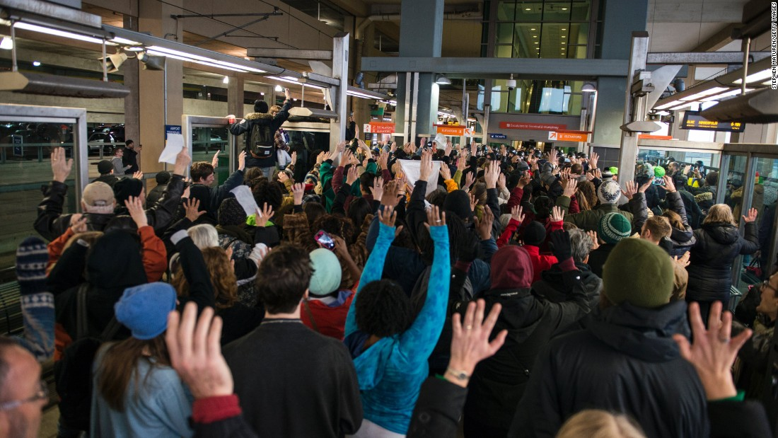 "Black Lives Matter protesters hold their hands in the air and chant, ""Hands up, don't shoot"" at the Minneapolis-St. Paul International Airport light rail stop in Minneapolis on Wednesday, December 23."