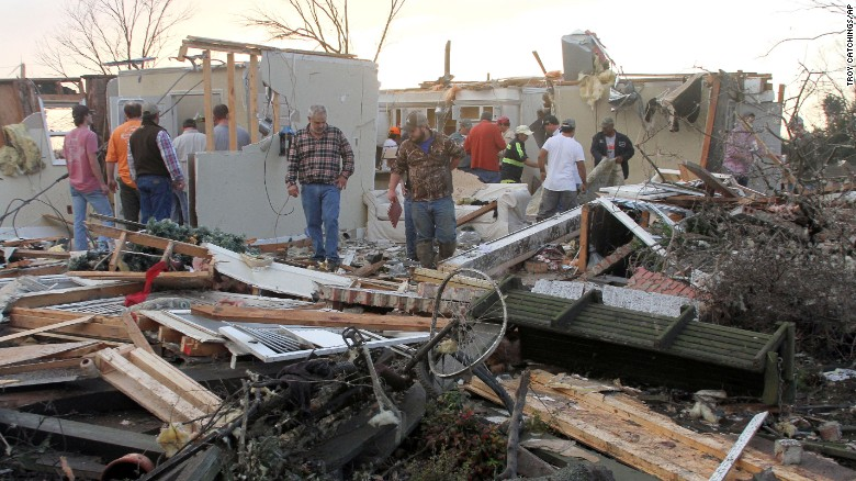 People inspect a storm-damaged home in the Roundaway community near Clarksdale, Miss., Wednesday, Dec. 23, 2015. A storm system forecasters called