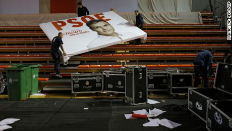 Workers carry a campaign sign for Spanish Socialist party leader Pedro Sanchez after a rally in Madrid on Saturday, December 19.