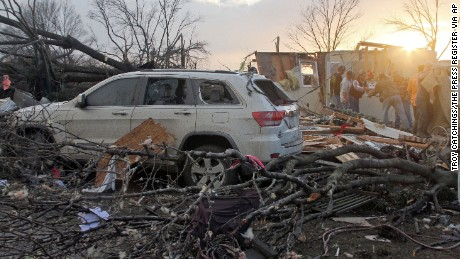 Neighbors help salvage items from a storm-damaged home in Roundaway, Mississippi, on Wednesday, December 23.