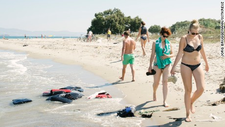 Tourists stroll the beach walk past abandoned lifejackets of refugees, August 2015 Kos, Kos Island, Greece, Europe